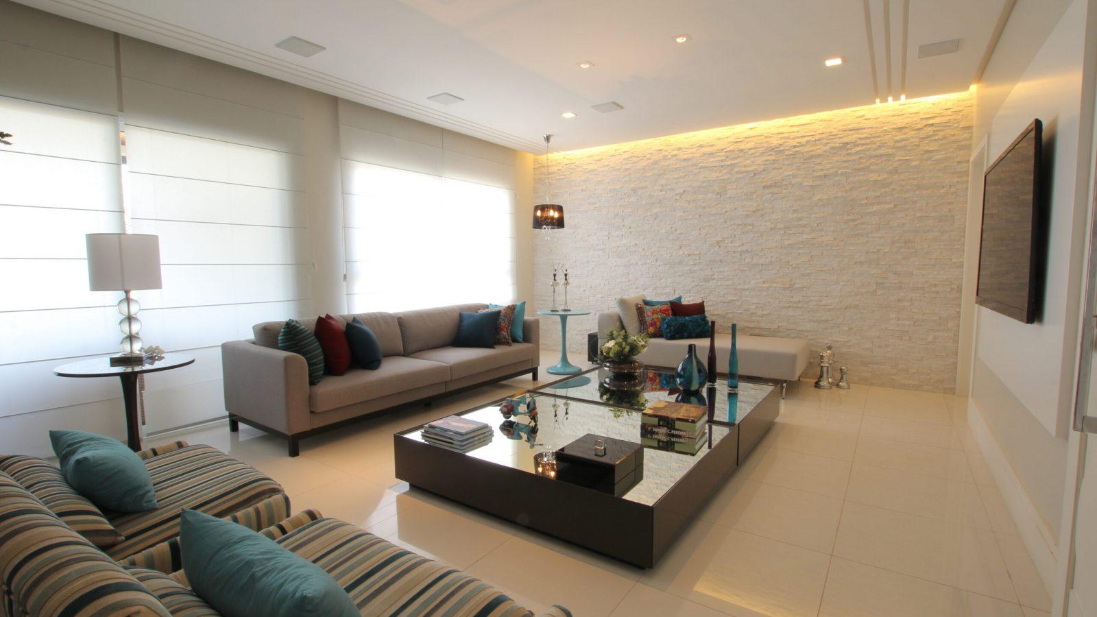 Lateral sala de estar, com duas poltronas e dois sofás. TV na parede.