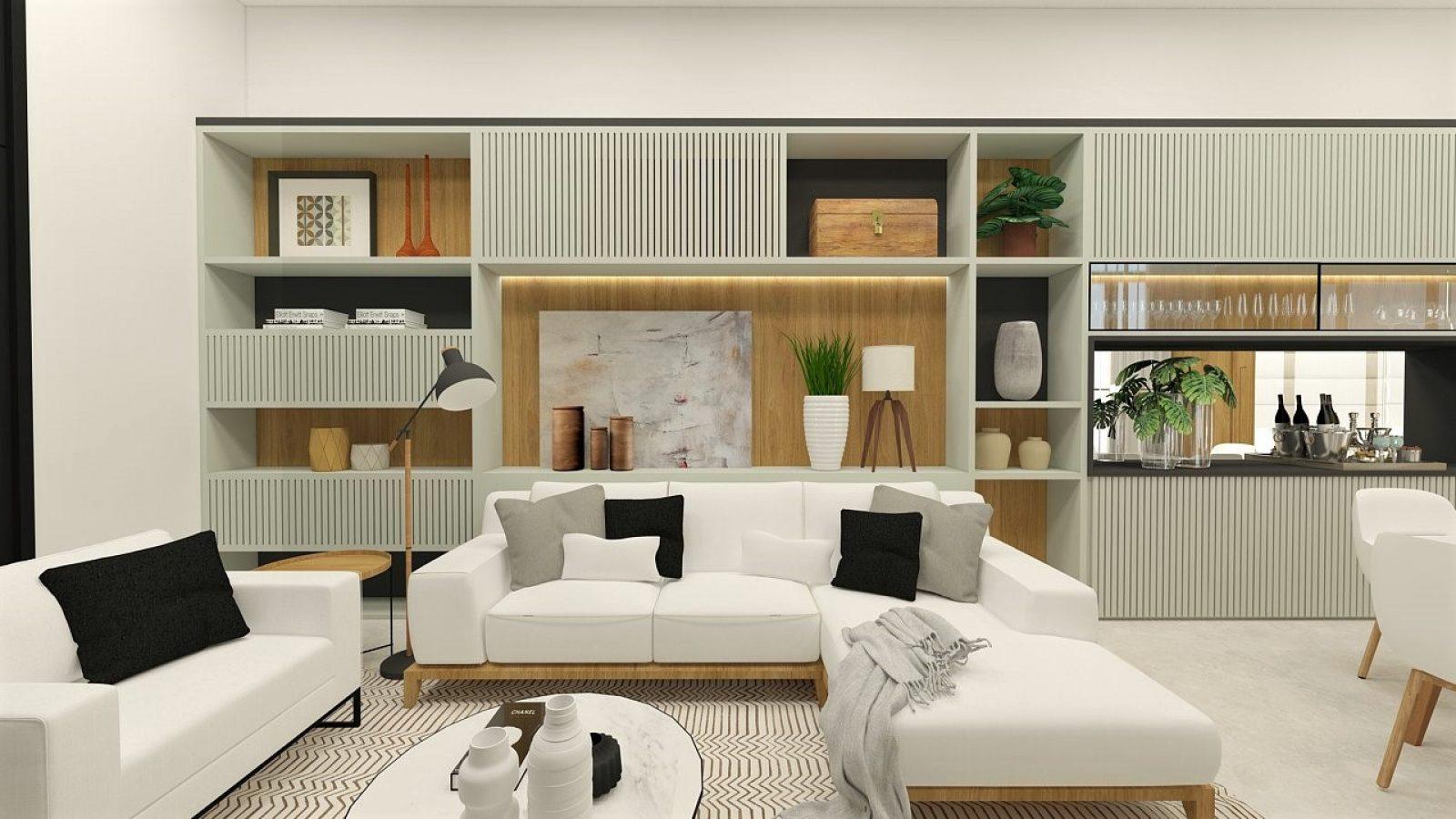 Sala de estar com sofás brancos e almofadas pretas. Estante com quadros e plantas ao fundo.