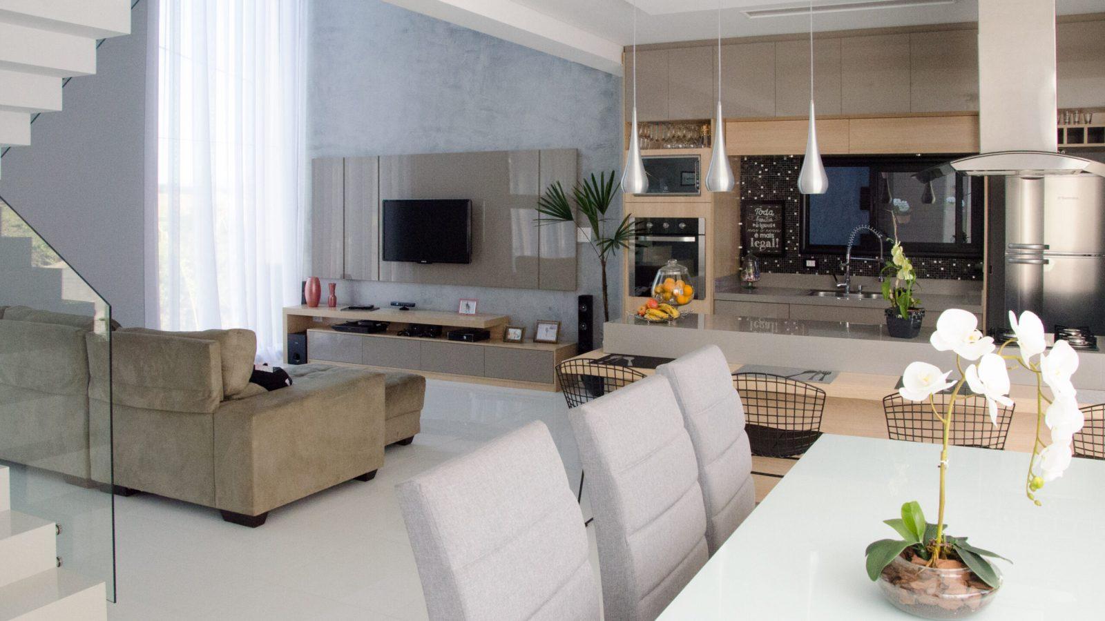 Sala de jantar com mesa e três cadeiras, com sala de estar ao fundo. Televisão e sofá marrom.