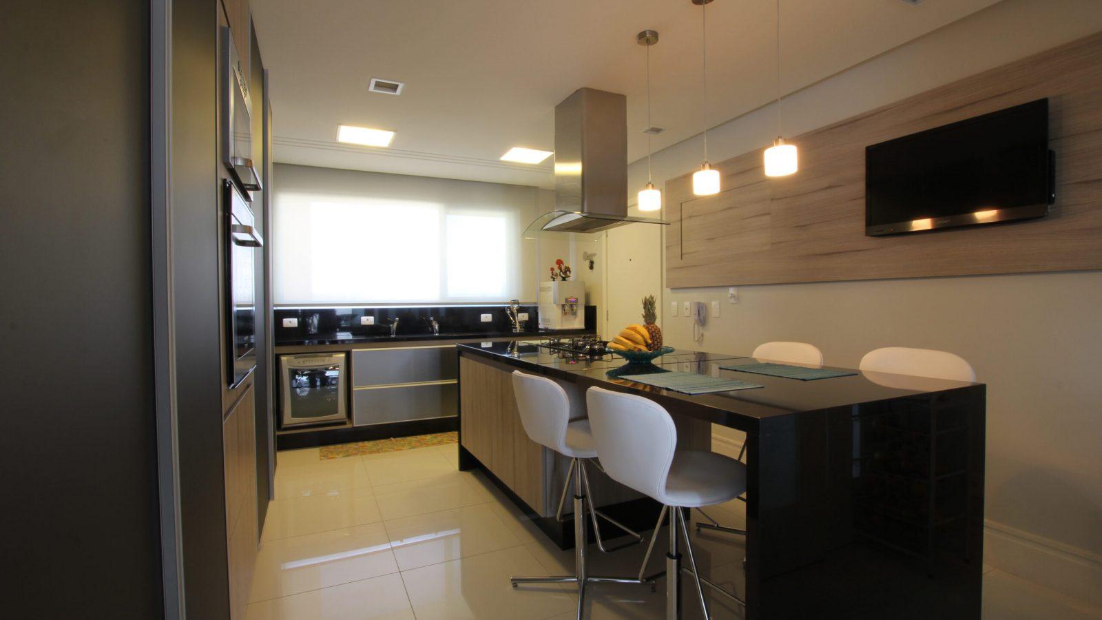 Cozinha com balcão preto no centro e cadeiras brancas. Televisão na parede e pia ao fundo.