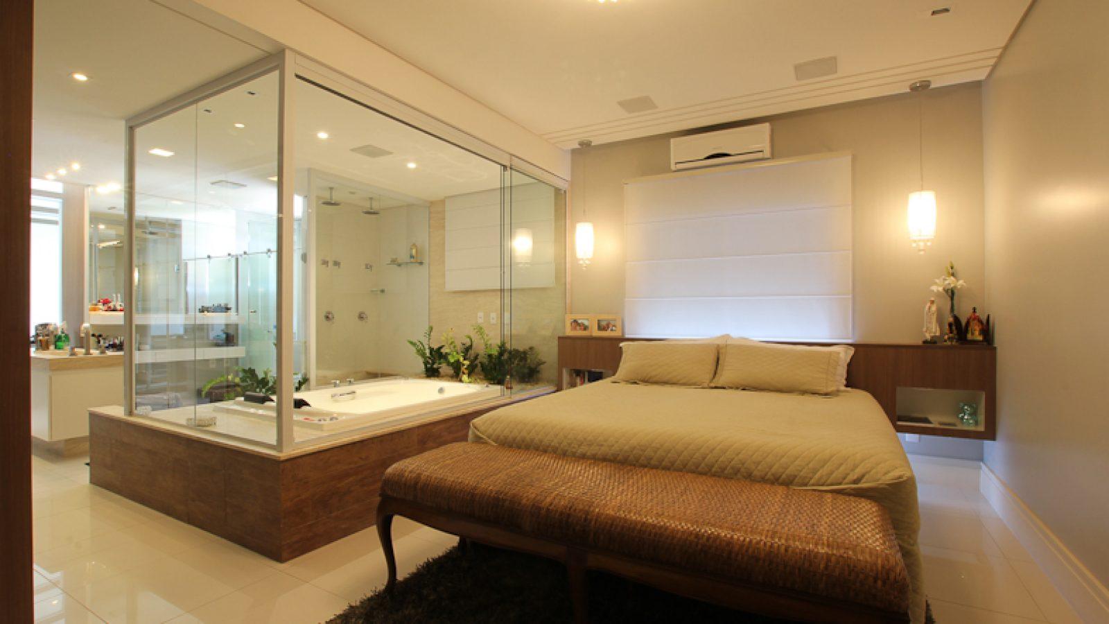 Quarto do casal, com cama de casal no centro e banheira ao lado da cama, com proteção em vidro.