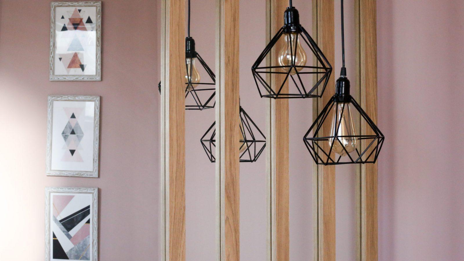 Luminárias pretas e parede com quadros ao fundo.